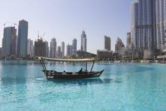 Tour boat Burj Khalifa Lake. Tourists take a boat ride near Dubai fountain show area, Dubai Mall and Burj Khalifa, in front of Souk Al Baha Royalty Free Stock Images