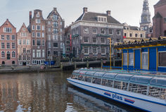 Tour boat and canal houses in Amsterdam Stock Photography