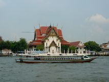 Tour Boat on the Chao Phraya River. A long sleek tour boat on the Chao Phraya River passes by one of the beautiful buildings of Bangkok, Thailand stock images