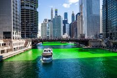 Tour boat crosses a dyed green Chicago River, which is surrounded by crowds. On St. Patricks` day royalty free stock photos