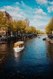 Tour Boat Cruising on one of the famous Amsterdam canals on the beautiful, sunny Autumn day. stock photo