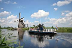 Tour boat at Kinderdijk. A tour boat taking visitors along the waterways at Kinderdijk, the Netherlands Royalty Free Stock Photography