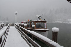 Tour boat on Konigssee lake at blizzard in winter time. Berchtesgaden, Bavaria, Germany. Royalty Free Stock Photo