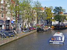 Tour boat navigates scenic Amsterdam canal. A tour boat navigates a central Amsterdam canal which is flanked by impressive heritage buildings that are emblematic stock photos