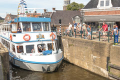 Tour boat by the old lock in Lemmer in Friesland in the north of Netherlands. Stock Image