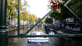 Tour boat sails in Amsterdam canal, Holland, Netherlands - view from canal bridge, wedding locks stock footage