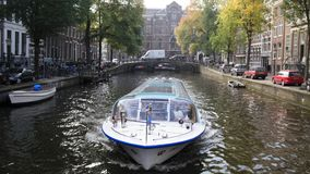Tour boat sails in Amsterdam canal, Holland, Netherlands stock footage