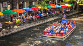 Tour Boat on the San Antonio River at the River Walk in San Anto. Tour boat full of tourists cruises down the San Antonio River at the River Walk in San Antonio royalty free stock photography