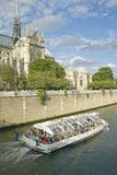 Tour Boat in the Seine River passing by Notre Dame Cathedral, Paris, France Stock Images