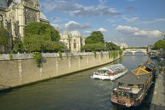 Tour Boat in the Seine River passing by Notre Dame Cathedral, Paris, France Stock Photography
