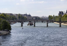 Tour boat on seine river. About to pass Pont des Arts bridge in Paris. Lovers` padlocks cram the railings of this arched bridge, offering panoramic views along stock photography