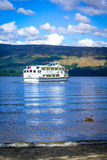 Tour boat on a sunny day at Loch Lomond lake in Luss, Scotland, 21 July, 2016 Royalty Free Stock Images