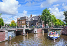 Tour boat with tourists on a canal, Amsterdam, Netherlands Royalty Free Stock Image