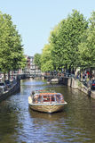 Tour boat with tourists on a canal, Amsterdam, Netherlands Stock Photography