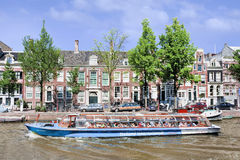 Tour boat with tourists on a canal, Amsterdam, netherlands Royalty Free Stock Photography