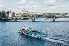 Tour boat on Vltava river in Prague, Czech Republic. Prague, Czech Republic - August 23, 2018: Tour boat on Vltava river in Prague, Prague Castle on the royalty free stock photos