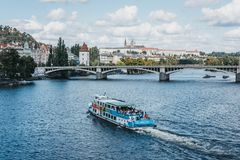 Tour boat on Vltava river in Prague, Czech Republic. Prague, Czech Republic - August 23, 2018: Tour boat on Vltava river in Prague, Prague Castle on the royalty free stock images