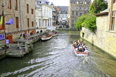 Tour Boats on the canal in Bruges,Belgium. Three tour boats loaded with tourists on the canal in Bruges, Belgium. The loading platform is on the left. Buildings Royalty Free Stock Image