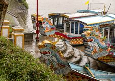 Tour boats with dragon heads, Hue Vietnam. Pictured are tour boats with dragon heads on the Perfume River in Hue, Vietnam. In Buddhism the dragon is the symbol royalty free stock photography