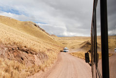 Tour bus along the Cusco-Puno Road, Peru. SACRED VALLEY OF THE INCAS, PERU - AUGUST 16, 2006: Tour bus running along the road following the Sacred Valley of the Stock Image
