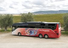 An tour bus with olive trees and fields of grape vines in the background at the  Tomaresca Tenuta Bocca di Lupo. Pictured is a tour bus with olive trees and Stock Photos