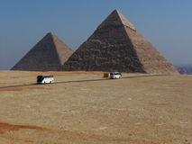 Tour Buses Criss Cross in Front of Khafre and Khufu Pyramids Stock Photo