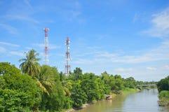 Tour cellulaire d'antenne dans la forêt près de la rivière et du ciel bleu Photos libres de droits