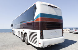 Tour Charter Bus. Rear and side view of parked tour charter bus along body of water Stock Photo