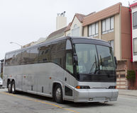 Tour Charter Bus. Side and front view of parked silver tour charter bus in residential neighborhood Royalty Free Stock Photos