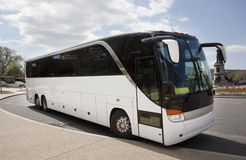Tour Charter Bus. Side and front view of parked white tour charter bus under blue sky with clouds Royalty Free Stock Photography