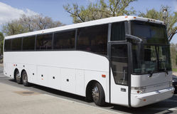 Tour Charter Bus. Side and front view of parked white tour charter bus under blue sky with clouds royalty free stock images