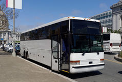 Tour Charter Bus. Side and front view of parked white tour charter bus in urban setting with door open Royalty Free Stock Photo