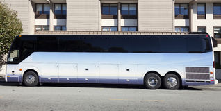 Tour Charter Bus. Side view of parked tour charter bus in front of urban building Royalty Free Stock Images