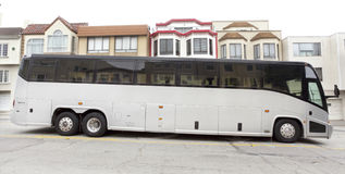 Tour Charter Bus. Side view of parked silver tour charter bus in residential neighborhood Stock Image