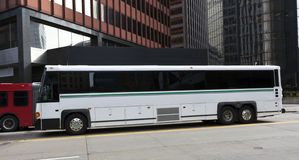 Tour Charter Bus. Side view of parked white tour charter bus in downtown urban setting Stock Photography