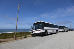 Tour Charter Buses. Front and side view of parked white tour charter buses along California Pacific coast Stock Photos