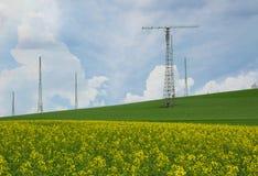 Tour d'émetteur au-dessus d'un gisement de floraison de graine de colza Photos stock