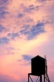 Tour d'eau rétro-éclairée contre le ciel de coucher du soleil à New York image stock