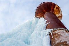 Tour d'eau rouillée couverte de la glace bleue à l'horaire d'hiver Photo libre de droits