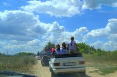 Tour d'enfants en voitures sur le chemin de terre Images libres de droits