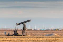 Tour d'huile dans un domaine d'or avec des turbines de vent à l'arrière-plan Photographie stock
