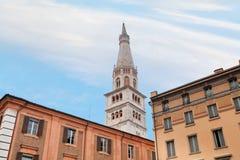 Tour de Bell de cathédrale de Modène sous les maisons urbaines Image stock