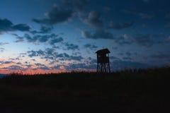 Tour de chasse, peau, surveillance dans le crépuscule avec le cloudscape photos stock