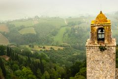 Tour de cloche antique donnant sur la campagne italienne chargée par brouillard images stock