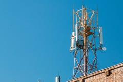 Tour de communication sur le toit d'un bâtiment contre le ciel bleu Images stock
