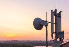 Tour de communications cellulaire sur un fond de la ville et un beau coucher du soleil en été Photo libre de droits