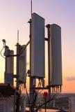 Tour de communications cellulaire sur un fond de la ville et un beau coucher du soleil en été Photos stock