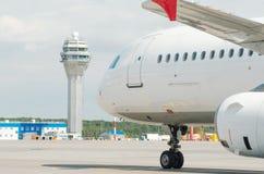 Tour de contrôle d'aéroport et bâtiments modernes terminaux avec le départ à enlever l'avion Photos stock