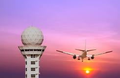 Tour de contrôle d'aéroport et atterrissage d'avion commercial au coucher du soleil Photos stock