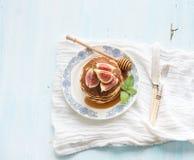 Tour de crêpe avec les figues et le miel frais d'un plat rustique Fond bleu-clair images stock